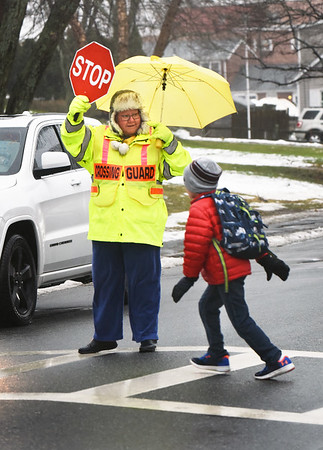 BRYAN EATON/Staff photo. Newburyport crossing guard Janet Crump greets youngsters as they leave the Bresnahan School while wearing a raincoat and holding an umbrella Monday afternoon. Rain is to continue today along with warmer weather.
