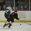 JIM VAIKNORAS/Staff photo Triton's Connor Kohan pushes the puck past Amesbury's  Cameron Chambers at the Graf Rink Wednesday night.