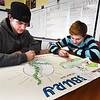 BRYAN EATON/Staff photo. Josh Conroy, 17, left, and Jared Proulx, 15, create a billboard from a smaller draft for the public relations campaign at the Amesbury Innovation High School.