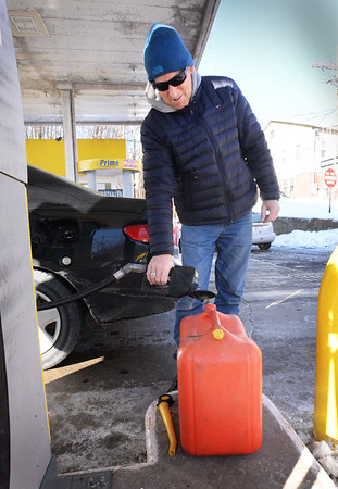 BRYAN EATON/Staff photo. After topping off the gas tank in his vehicle, Jon Aponas of Amesbury fills up a portable tank at A1 Prime gas station in Amesbury for use in his snowblower.