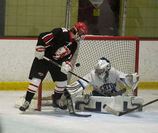 JIM VAIKNORAS/Staff photo Triton's Ben Fougere makes a save on Amesbury's Blake Bennett at the Graf Rink Wednesday night.