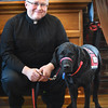 BRYAN EATON/Staff photo. Father Scott A. Euvrard of Holy Family Parish with Lazer.