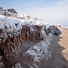 JIM VAIKNORAS/Staff photo A man walks along a 5 ft cliff in the dune caused by storm erosion on Salisbury Beach