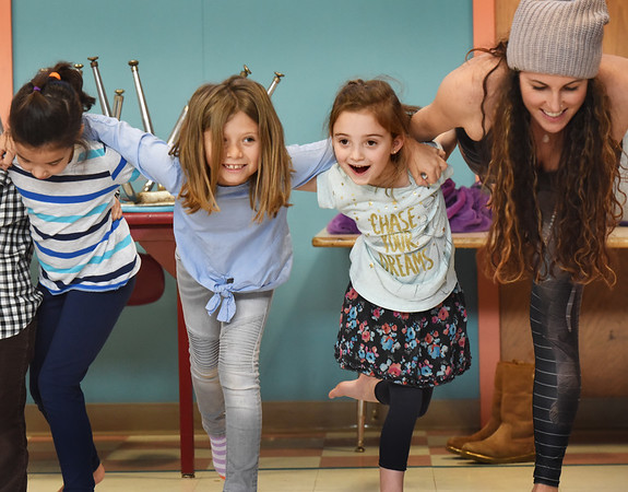 BRYAN EATON/Staff photo. Instructor Elissa Shoreman, right, and her 10 students lock arms, stand on one leg and bend forward in one of their excercises. From left, Addison Moore, 6, Finley Goodrich, 8, and Emme Lupa, 6.