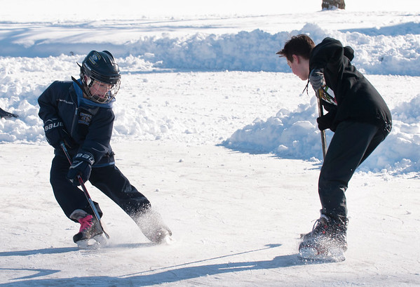 JIM VAIKNORAS/Staff photo  Callan Wardwell  fights for the puck with Josh Montiro during a pick-up hockey game on the Upper Green in Newbury Thursday. The boys are classmates at Triton Middle School.