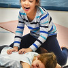 "BRYAN EATON/Staff photo. Elissa Shoreman of Buddhaful Souls Yoga Studio in Rowley has been giving yoga lessons in Newbury Elementary School's Explorations Afterschool program on Monday afternoon. Near the end of the session they partner up for ""cookie dough massage"" where students, knead, pound, and cut out the ""cookie dough"" to the delight here of Addison Moore, top, and Emme Lupa, both 6."