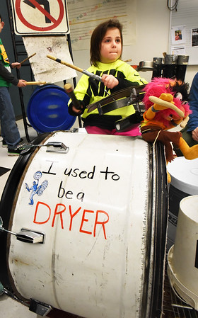BRYAN EATON/Staff photo. Mackenzie Andrews, 8, bangs away at instruments attached to a larger drum that Irwin created from an old clothes dryer drum.