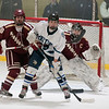 JIM VAIKNORAS/Staff photo Newburyport goalie Kenneth Hodge looks around Newburyport's Matthew Donlan and Hogg Triton's Will Rennick Saturday at the Graf Rink in Newburyport.