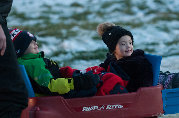 JIM VAIKNORAS/Staff photo Connor Bush, 4, and his sister Caroline, 2, gets ride around at the Old Newbury Christmas tree Bonfire at the Tendercrop Farm fields and Spencer Perce-Little Farm in Newbury Saturday night.
