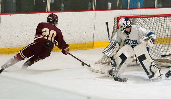 JIM VAIKNORAS/Staff photo Newburyport's Jacob Gossi-Hogg controls the puck behind Triton goalie Jamie Szmanski Saturday at the Graf Rink in Newburyport.