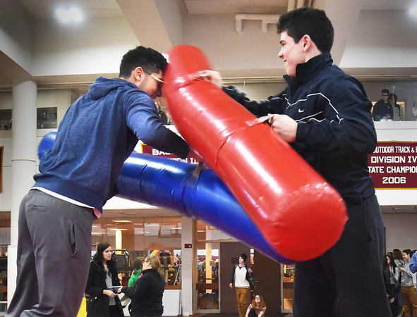 "BRYAN EATON/Staff photo. Andrew Wellmann, 17, left, and Seamus Webster, 16, compete in ""inflatable jousting"" at the Newburyport High School. The high school partnered with Newburyport Youth Services to create the first-ever ""stress free zone"" in the school's gymnasium during midterm exams."