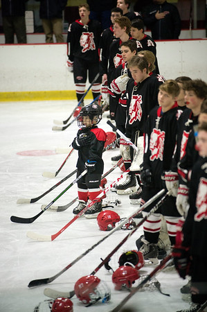 JIM VAIKNORAS/Staff photo An Amesbury Youth Hockey players puts his hand over his heart as he stand with the Amesbury High School team during the playing of the National Anthem Wednesday night before the Indian's game against Triton at the Graf Rink in Newburyport.