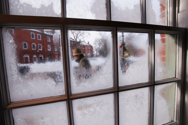 JIM VAIKNORAS/Staff photo A man walks up State Street in Newburyport on a cold Saturday morning as seen through frozen windows at Starbucks in Market Square in Newburyport.