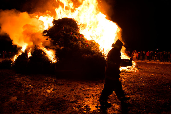 JIM VAIKNORAS/Staff photo A fire fighter walks past the burning trees at the Old Newbury Christmas tree Bonfire at the Tendercrop Farm fields and Spencer Perce-Little Farm in Newbury Saturday night.
