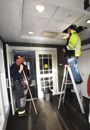 BRYAN EATON/Staff photo. Ray Cote of the Salisbury DPW and the town fire department check out the ceiling in the vestibule near the meeting room of the Salisbury Public Library where a burst pipe caused some damage.