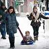 BRYAN EATON/Staff photo. Lyla Ericson, 2, of Newburyport gets pulled in a sled down the sidewalk on Newburyport's State Street by her aunt Molly Ericson of Amesbury with other aunt, Stephanie Ericson of Newburyport. They had been at the Newuryport Public Library late Wednesday morning.