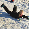 "BRYAN EATON/Staff photo. Layla LeClair does a little ""belly sledding"" at the hill on the grounds of the Bresnahan School in Newburyport. She was at the YWCA Afterschool program where she and others headed outdoors after snack time."