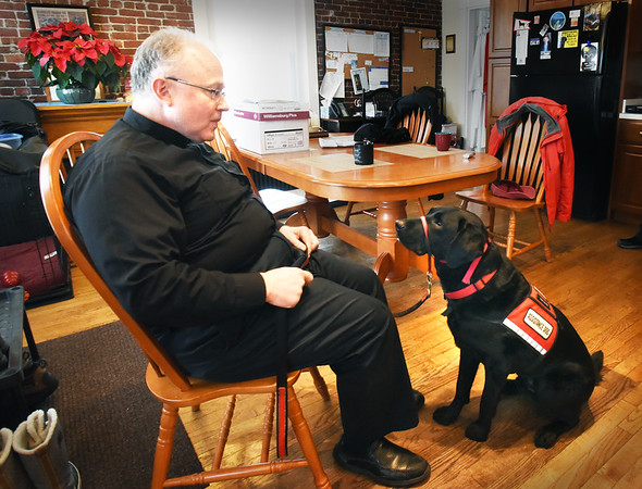 "BRYAN EATON/Staff photo. Father Scott A. Euvrard has Lazer trained when in nursing homes that when he says ""visit"" the dog will lay his head on the person's lap."