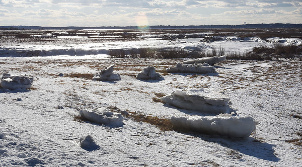 BRYAN EATON/Staff photo. Ice floes are deposited on the marsh along the roadway at Salisbury Beach State Reservation showing how high the tide was during last Thursday's storm.
