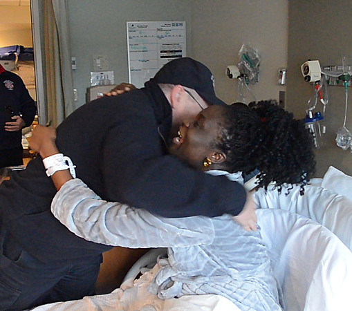 JIM VAIKNORAS/Staff photo Memory Chihwayi of Merrimac hugs Newburyport Fire fighter Bob Morse in her room at the Anna Jaques. Morse along with 3 of his co-workers delivered Memory's baby, Jayden Matombo in front of Station #2 Thursday.