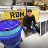 BRYAN EATON/Staff photo. Visible Good owner, John Rossi shows a moblie solar electric unit, water filtration device, left, which can purify over 80 gallons of water a day, and an unassembled shelter, behind.