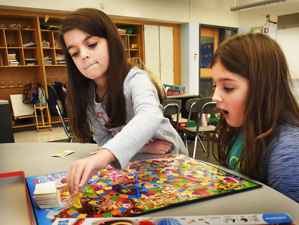 BRYAN EATON/Staff photo. Addison Murphy, 7, left, gets the win in this round of Candy Land with Jocelyn Zarella, also 7. They were in board game room in the Salisbury Elementary Afterschool program Explorations which also features basketball, Lego's, theater among other activities.