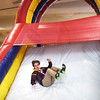 BRYAN EATON/Staff photo. Jack Breighner, 15, comes down the slide at the end of the obstacle course.