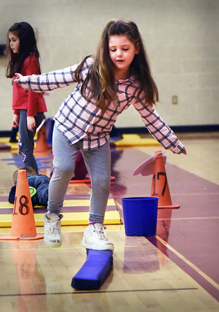 BRYAN EATON/Staff photo. Jennavive Coughlin, 5, tries to stay upright as she moves along a balance beam in physical education class at the Bresnahan School. The kindergartners were doing Tabata, a Japanese created style of fitness and skill stations.