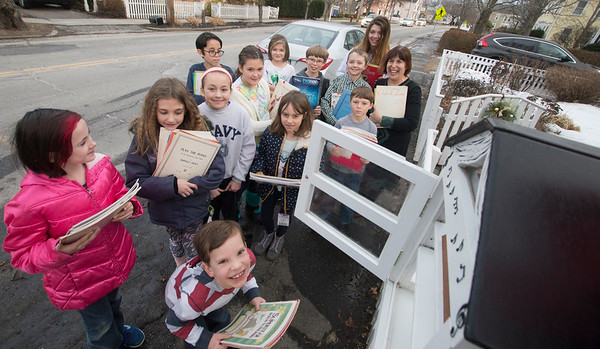 JIM VAIKNORAS/Staff photo Piano Teach  Penny Lazarus and her students put music  a free library in front of Lazarus's house on Merrimac Street in Newburyport Saturday.
