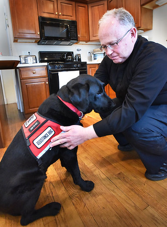BRYAN EATON/Staff photo. Father Scott A. Euvrard fits Lazer with his gear.