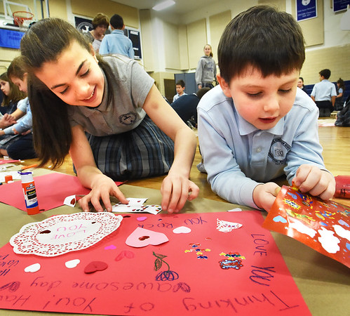 BRYAN EATON/Staff photo. Older students at the Immaculate Conception School in Newburyport teamed up with younger ones to create Valentine placemats which will be laminated and given to residents of nursing homes and veterans groups, as a community service project for Catholic School Week. Eighth-grader Olivia D'Ambrosio, 13, picks out stickers with kindergartner Thomas Kelcourse, 6, on Tuesday morning.