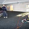 BRYAN EATON/Staff photo. Salisbury firefighters vacuum and squeegee the floor in the community room at the Salisbury Public Library after a pipe burst Wednesday afternoon.