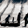 JIM VAIKNORAS/Staff photo Tubers silhouetted by the morning sun make their way towards the lift to go back up up the hill Sunday. The warm weather Friday and Saturday melted most of the area snow
