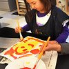 BRYAN EATON/Staff photo. Jessica Heller, 5, uses red paint on a yellow background creating an orange face at the Bresnahan School on Monday morning. The Newburyport preschooler was in Pam Jamison's art class where they were learning about primary colors.