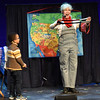 "BRYAN EATON/Staff photo. With the help of Adrian Kesselly using a magic wand, Debbie O'Carroll turned three bands into one during her Railroad Magic Show she presented at the Firehouse Center for th entire Newburyport Montessori School on Thursday morning. In her words the show ""features participatory stage magic, zany comedy and some renowned heroes, superheroes, unlikely heroes and everyday men and women who intrigue and inspire."""
