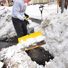 BRYAN EATON/Staff photo. George MacDougall cleans out the storm drain in front of his home on the corner of Merrimac and Butler Streetsin Newburyport. The retiree says that during heavy rains, which is forecast for today and tomorrow,flooding can occur and can get worse when snow is on the ground. Much of Merrimac and Water Streets are at the bottom of a network of main and side streets which water pours down to cause the flooding.