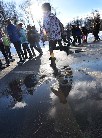 BRYAN EATON/Staff photo. Students at Newbury Elementary School reflect in puddles of melting snow as they had recess outdoors on Tuesday afternoon. The melting should continue as daytime temperatures stay above freezing and rain due into the weekend.