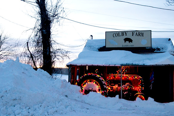 JIM VAIKNORAS/Staff photo Snow is piles up in front of a tractor still decorated with holiday lights at the Colby Farm in Newbury as the sun sets Saturday afternoon