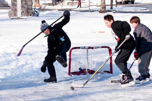 JIM VAIKNORAS/Staff photo Jack Hathaway,13 takes a stumble after making a save on Callan Wardwell , 12, and Luca Wardwell, 10, during a pick-up hockey game on the Upper Green in Newbury Thursday. The Boys are classmates at Triton Middle School.