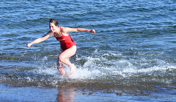 BRYAN EATON/Staff photo. Janet Perkins-Rowland of Durham, N.H. seems elated to jump out of the 44 degree ocean at Salisbury Beach yesterday. She was running in the Winner's Circle Running Club's Hangover Classic, a 5K and 10K race.