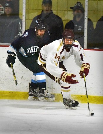 BRYAN EATON/Staff photo. Newburyport's Declan Sullivan pulls the puck out of the Newburyport end as Triton'sTJ Regan moves in.