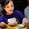 BRYAN EATON/Staff photo. Audrey Paciulan, 7, tries her hand at creating an egg roll of turkey sausage and Oriental vegetables at the Newburyport Rec Center on Monday. She was taking Cook's Corner cooking class this week being taught by Fran Kaplan.