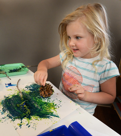 "BRYAN EATON/Staff photo. Elizabeth Kerr, 3, of Newburyport uses a pinecone as a paintbrush at a summer program at the Newburyport Montessori School. The theme of this week's camp is ""I Am Back and Explorer"" the children finding items on a little hike and then creating art with them."