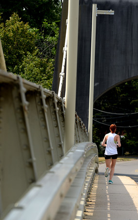 JIM VAIKNORAS/Staff photo A runner makes her way across the Chain Bridge connecting Amesbury to Newburyport Sunday morning.