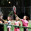 BRYAN EATON/Staff photo. Youngsters are taking tennis lessons this week at Atkinson Common through the Newburyport Youth Services summer programs. Here counselor Ann DeKanter lobs balls at them and if they miss, they have to go to the end of the line and work their way back up again as they learn some basics.