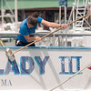 JIM VAIKNORAS/Staff photo Amy Warren, a crew member on the Captain's Lady III washes scrubs the stern of the ship as it sits on the Newburyport waterfront Sunday morning.Amy is a biologist and the Naturalist on the whale watching vessel.