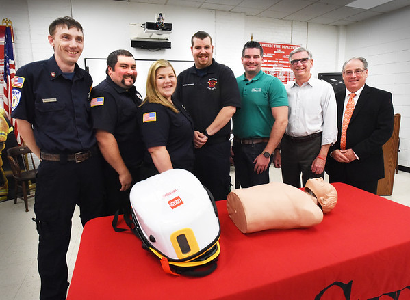 BRYAN EATON/Staff photo. The Merrimac Fire Department has purchased a Lucas 3 chest compression system, at left of mannequin, with donations from the community and major donors. From left, firefighters who were on the fundraising committee, Will Howard, Brandon Cox, Nicole Richard and Shane Sevigny with Eric and Rick Fournier of 1st Payroll and Haverhill Bank president and CEO Thomas L. Mortimer. Missing from photo are representatives of Salter Bus Company.