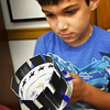 BRYAN EATON/Staff photo. Anthony Peixoto, 6, of Amesbury spins a zeotrope which he made at the Children's Room at the Amesbury Public Library during craft time which meets on Monday mornings. The early animation invention appears to show a horse as is gallops as he looks through the slats in the side.