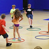 BRYAN EATON/Staff photo. The music stops and youngsters scramble to find an open hula hoop to stand in, a version of Musical Chairs on Monday afternoon at the Boys and Girls Club. There will definitely be outdoor water games later this week as temperatures reach the 90's.