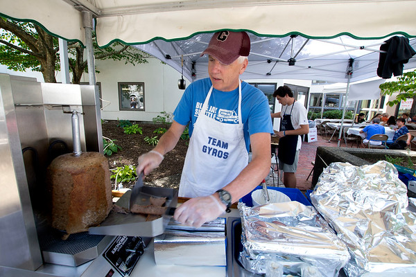 JIM VAIKNORAS/Staff photo Eddie Connor of Newburyport slices gyros at the Greek Food Festival Friday at the Annunciation Greek Orthodox Church on Harris Street in Newburyport. Luke George is Grilling them up in the back ground.